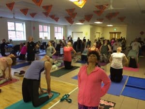 Tabitha Wright female yoga teacher leading group of people in a yoga class