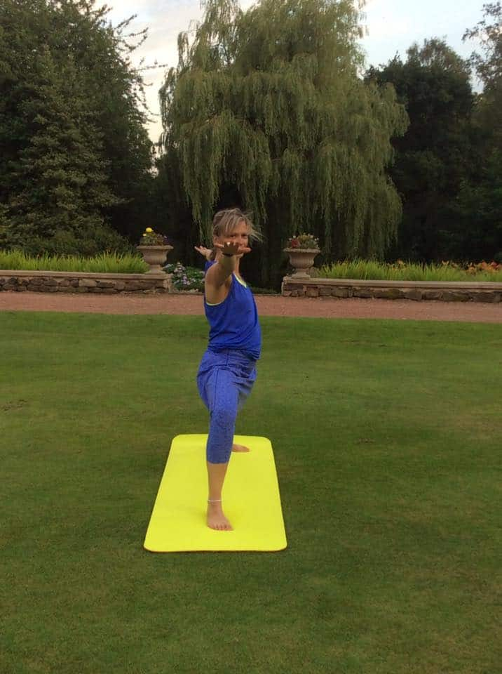 Tabitha yoga teacher standing in a yoga pose practising yoga outdoors