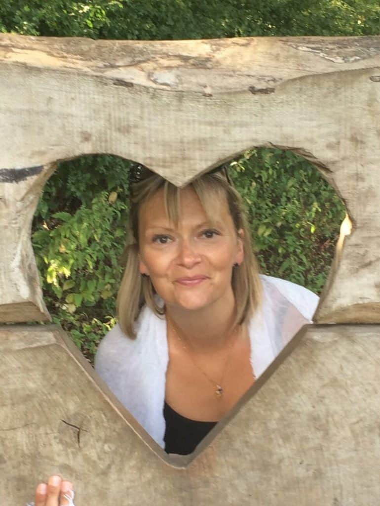 Tabitha Wright Yoga Teacher sitting in a love heart shaped frame in her self love article