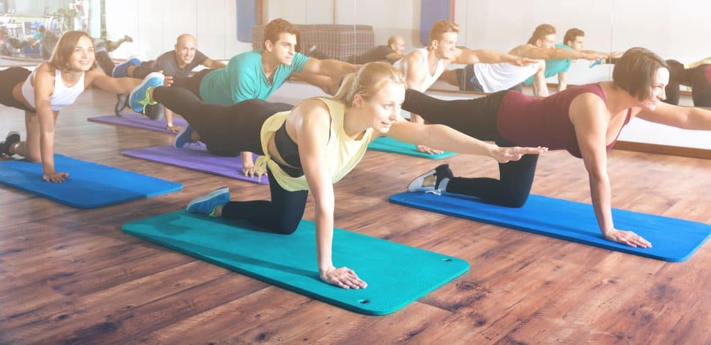 group of happy people exercising in a yoga and Pilates class