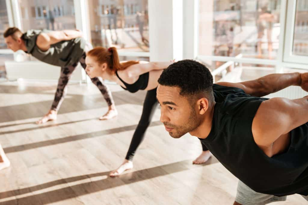 concentrated African American young man standing in a yoga pose in a yoga & Pilates class