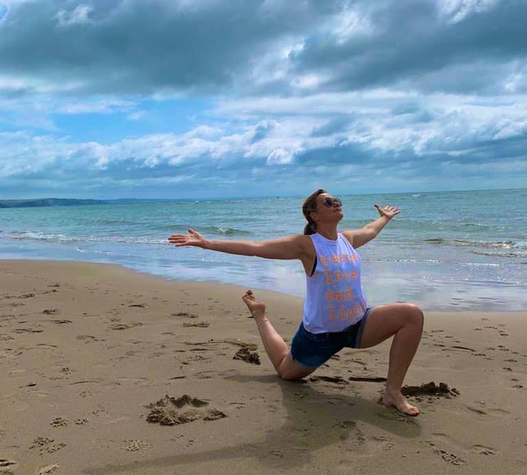 tabitha wright kneeling in a yoga pose on the beach