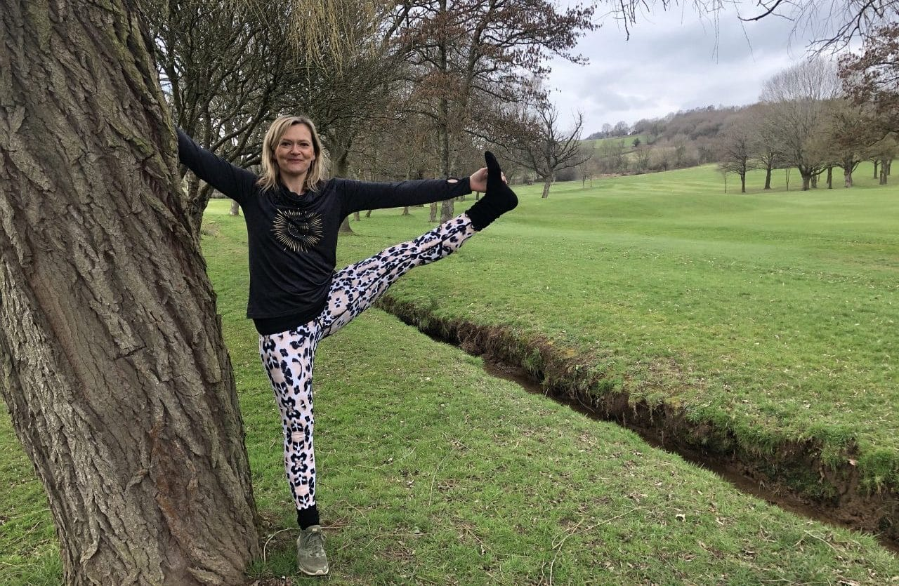 tabitha wright standing in tree yoga pose on and Autumn day in the countryside