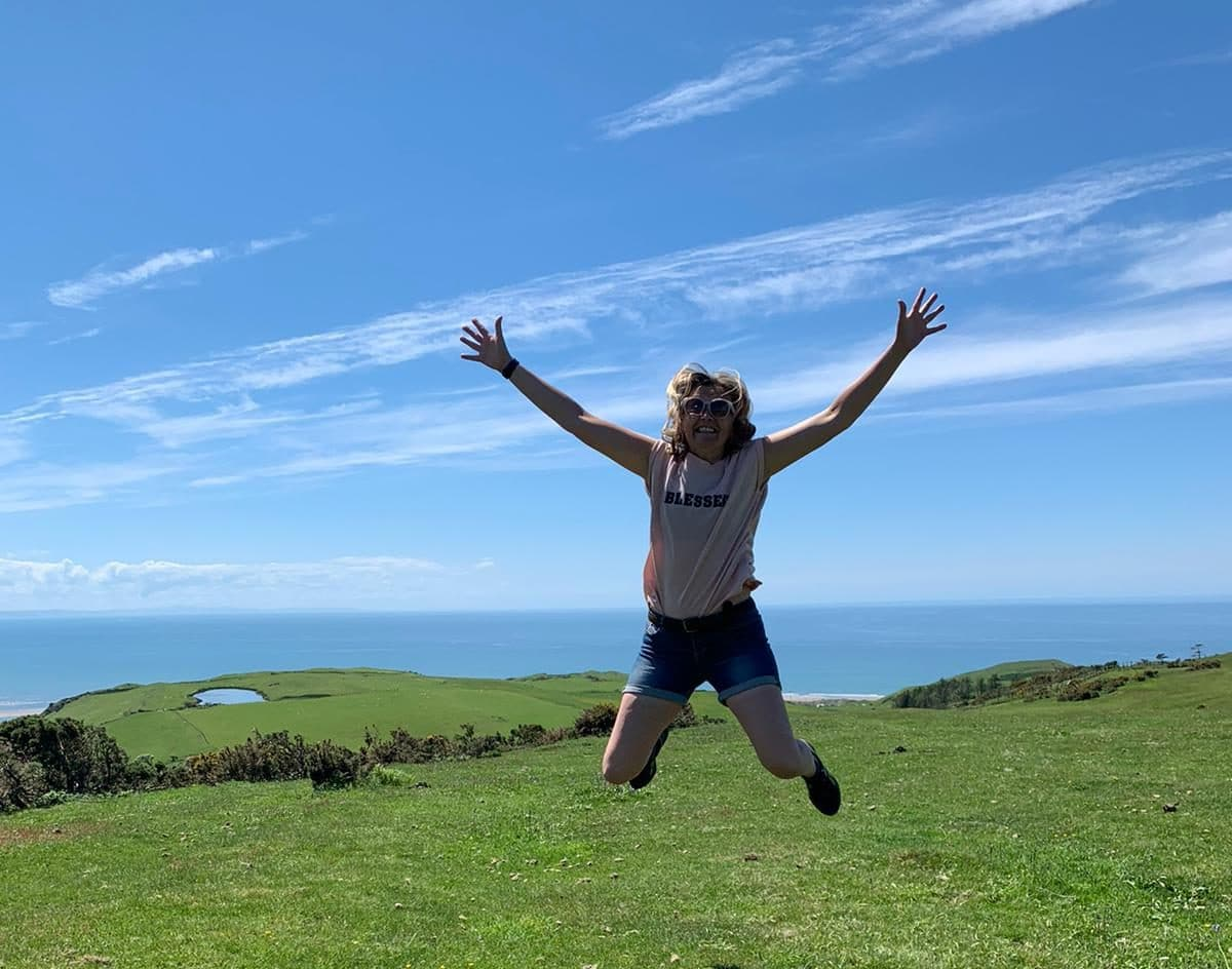 tabitha wright jumping in the air at the coast