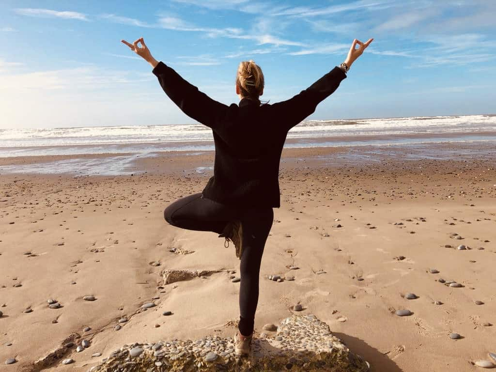 Tabitha Wright standing in tree yoga pose on the beach
