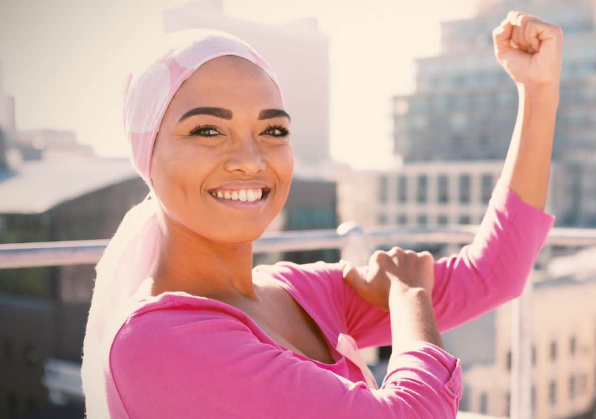 young woman with a scarf on her head that looks like a cancer patient holding her arm up in the air in a muscle pose