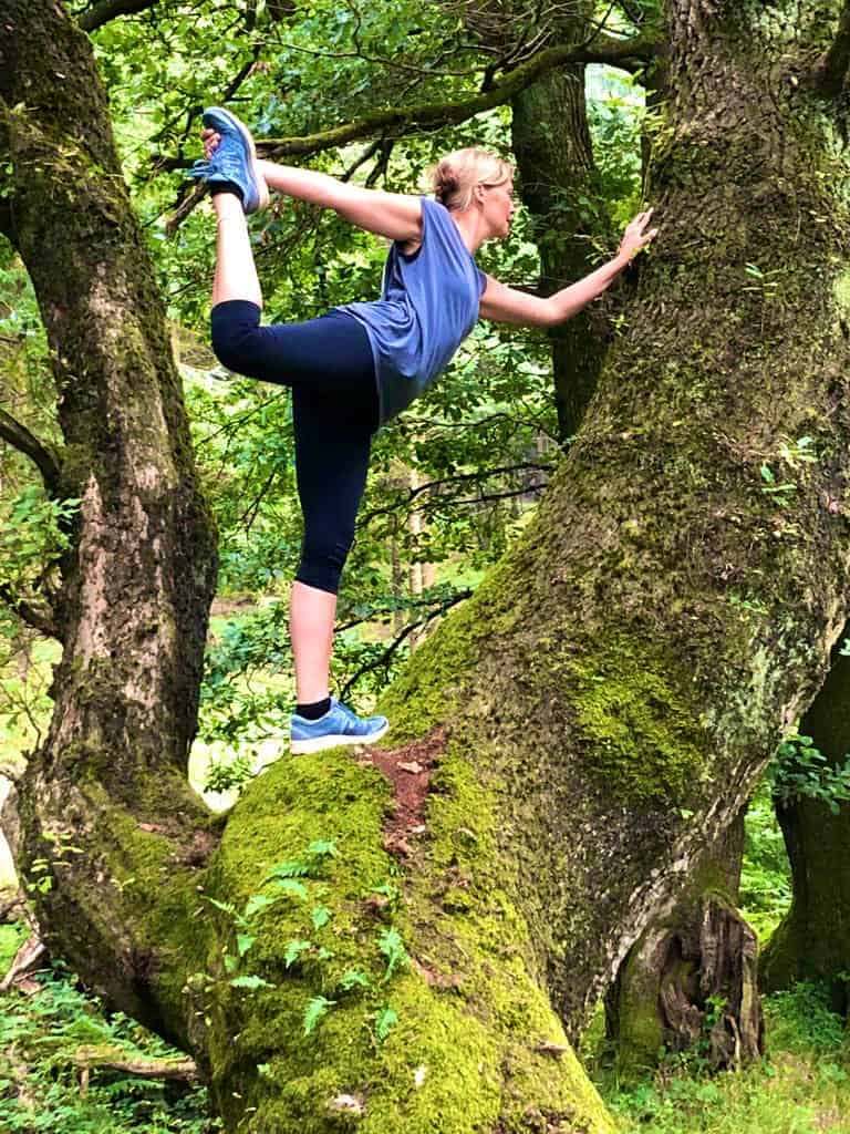Tabitha Wright, yoga teacher at Tabitha Yoga in dancers pose in a tree in the forest