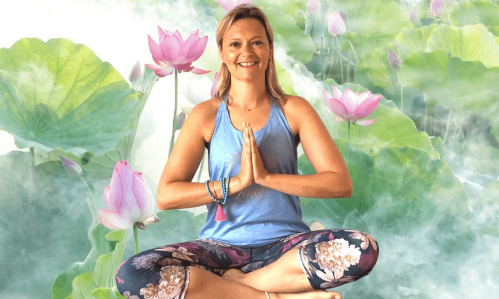 Tabitha Wright female yoga teacher sitting cross-legged in Namaste yoga position