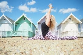 woman sitting in a yoga pose on the beach