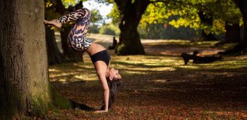 woman in a yoga inversion against a tree yogaleggs