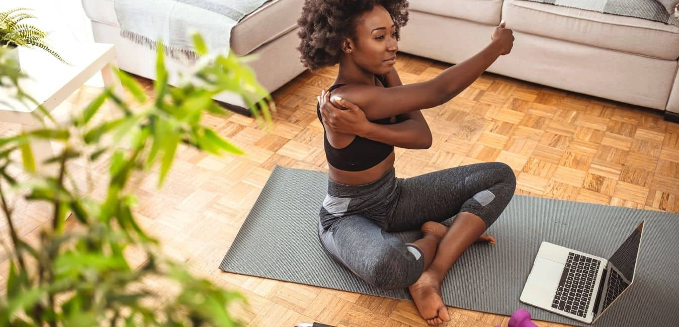 woman stretching while doing yoga online at home